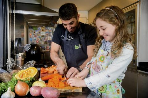 Coronavirus (COVID-19): helathy eating at home. A girl prepares food with her stepfather in Uruguay.