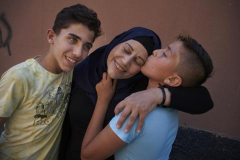 Two Syrian boys embrace and kiss their mother.