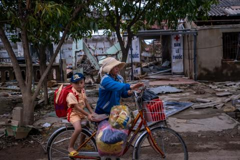 A woman carries her son on bicycle with goods received from donors in An Thuy Commune, Le Thuy District, Quang Binh Province, Vietnam on October 26, 2020.