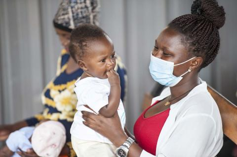 A mother and her child await immunization at the Komamboga Health Centre III in Uganda.