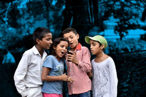Four children look at a mobile phone