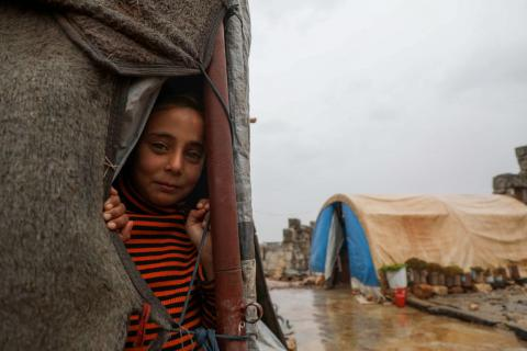 Syria. A girl looks out from a tent at a refugee camp.