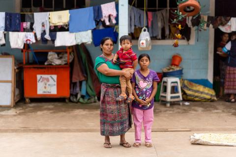Guatemala. A family stand outside a shelter.