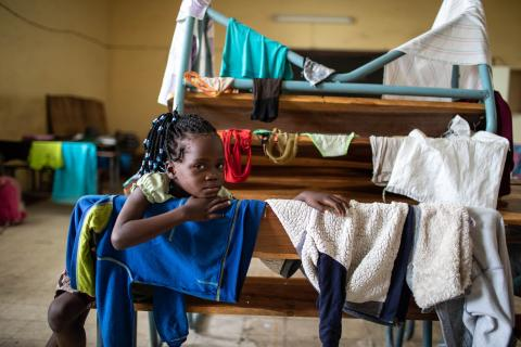 Mozambique. A girl sits surrounded by her clothes at a shelter.