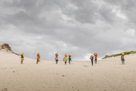 Children walk on sand carrying water
