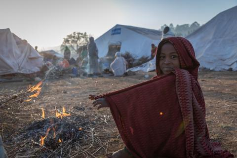 Ethiopia. A girl warms her hands near a fire at a site for internally displaced persons.