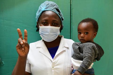 Vaccines for all: A nurse holding a child in a hospital in Cameroon.