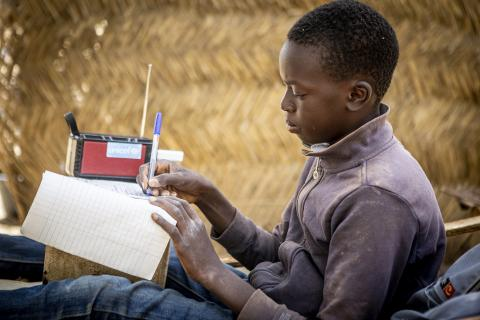 Mali. A boy listens to a radio while he studies.
