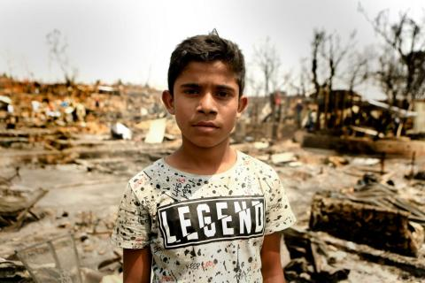 Bangladesh. A refugee child stands near the remains left by a fire.