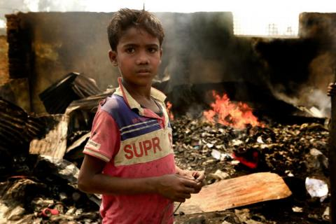 Bangladesh. A boy stands near the aftermath of a fire.
