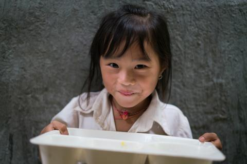 A young girl in Vietnam holds her lunch tray at her primary school.