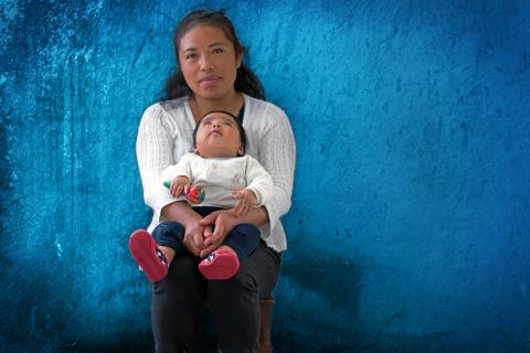 A woman holds a child in her lap, Mexico