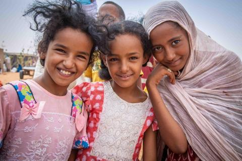 Three Malian girls pose outside the food distribution center in Mbera camp.