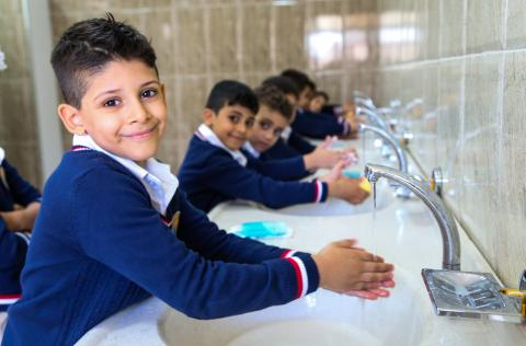 Children wash their hands in school.