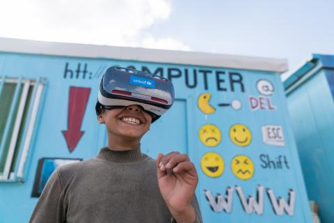 Mansoor,12, watches the virtual reality documentary 'Clouds over Sidra' with a big grin, outside a UNICEF-supported Makani centre in the Za'atari camp for Syrian refugees, in Mafraq Governorate, near the Syrian border.