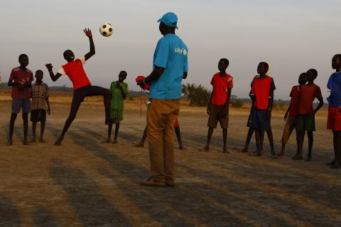 Children in South Sudan play football as the sun goes down over the field.