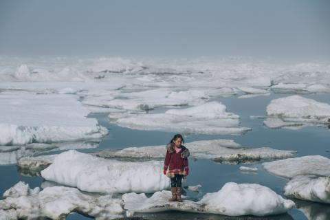 Alaska, United States: a girl wearing a red coat stands on an ice floe.