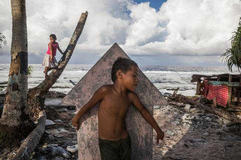 Children play 'hide and seek' in Teone's graveyard in Tuvalu, 2015. Massive coastal erosion in Teone caused many coconut trees to fall down.