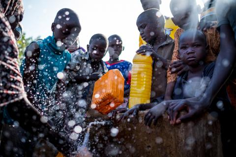 Children fill jerry cans with water at a tap inside the Dalori camp in Maiduguri, Nigeria,