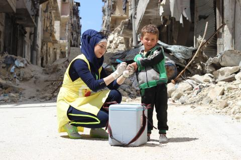 A woman vaccinates a child, Syria