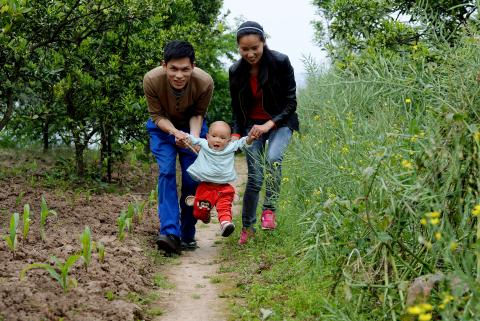Two parents walking down a dirt path near the woods play with their young son.