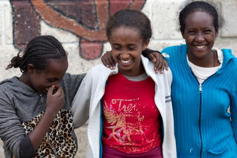 Three girls laugh with their arms around each other, Ethiopia