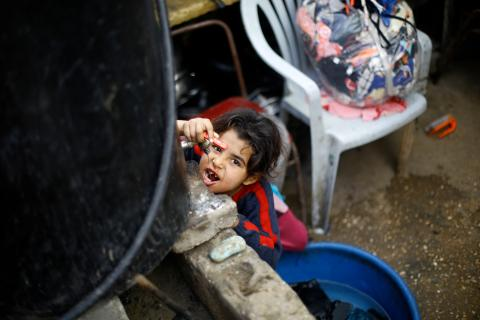 Eight-year-old Sawsan drinks water from a container outside the tin-roofed shack