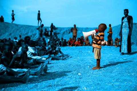 A young boy sings into a megaphone, South Sudan