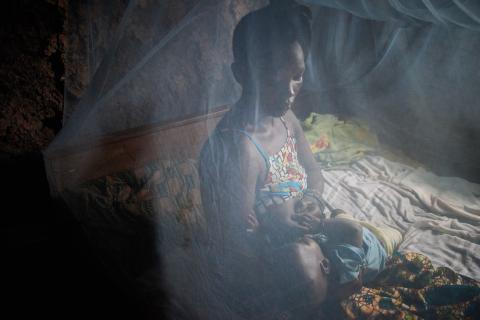 A woman and her child sit on a bed under a mosquito net, Sierra Leone