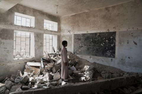 A young child stands in a classroom of rubble in Saada, Yemen, staring at what used to be a chalkboard.