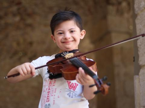 Eight-year-old Somar beams while playing the violin