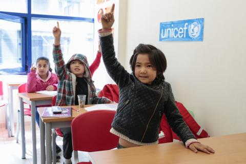 Afghanistan. Children raise their hands in class.
