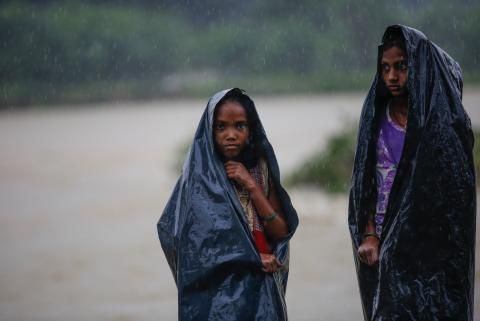 Two girls use plastic sheets to hide from the rain in Nepal
