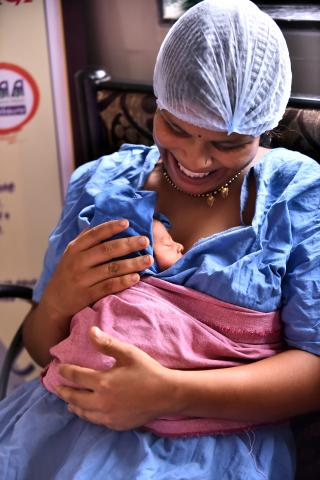 A woman holds her newborn baby in India