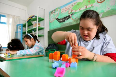 A girl who has Down's syndrome plays with building blocks