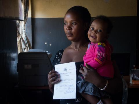A mother displays her child's birth certificate while holding her child in a hospital in Uganda.