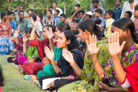 young girls raise their hands to take a pledge against child marriage