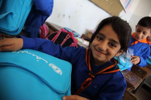 In the Syrian Arab Republic, a girl in Grade 3 looks at the school bag and stationery supplies she has just received at her school in central Damascus, the capital.