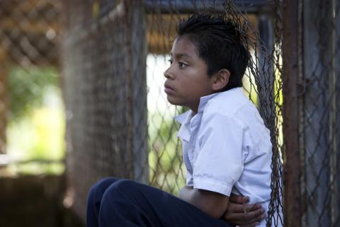 A boy sitting back against a wired fence at school in El Salvador