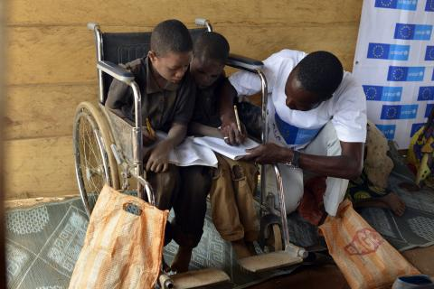 Two boys with disabilities, who are sharing a wheelchair, get help from their teacher during a primary-school class in a learning and protection space at the Gado site for refugees from the Central African Republic, in East Region.