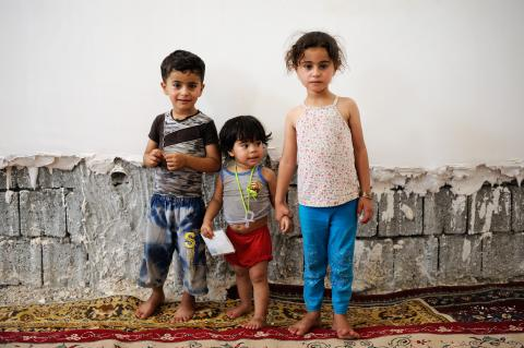 Naem, 4, Aya, 2 and Duna, 6 (from left to right), displaced siblings from Ramadi, wait for their father inside Thi Al-Norain Mosque in Kirkuk.