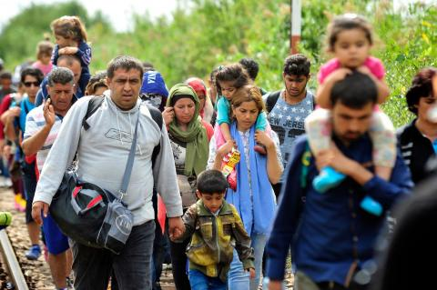 Refugee and migrant families walk along the railway tracks