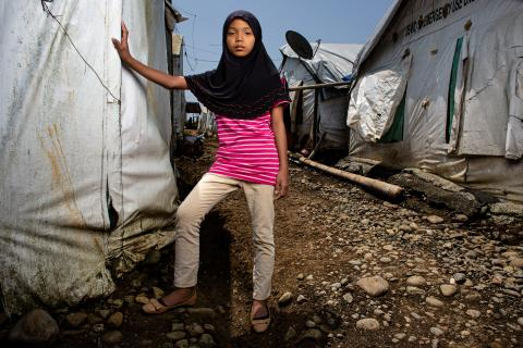 Marawi. A girl stands next to her family's temporary home in a tented evacuation site.