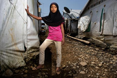 Philippines. A girl stands next to her family's temporary home.