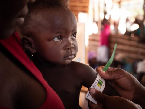 On 27 September, 2019, a girl has her mid-upper arm circumference measured by a health worker during a checkup at a community outreach medical clinic near the village of Mecufi, in northern Mozambique.