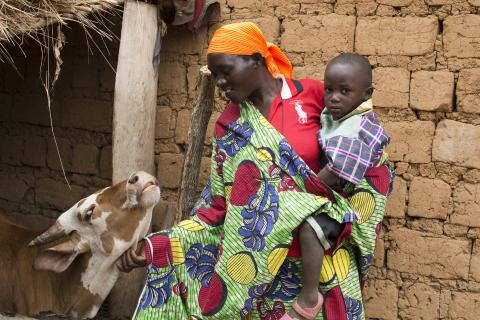 A woman in Burundi holds her son on her hip as she pets a cow.