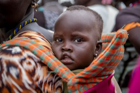 South Sudan. A baby sits strapped to his mother's back.