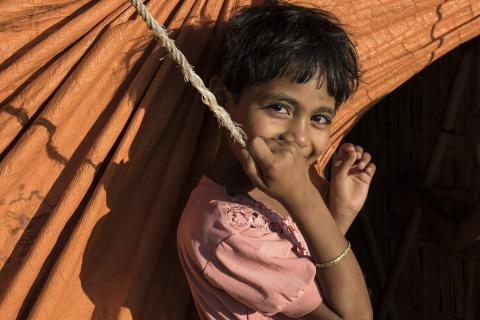 A girl smiles next to her home in the Balukhali refugee camp in Cox's Bazar, Bangladesh, in 2019.