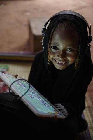 A girl child smiles while using her tablet and headphones in Eastern Sudan in 2019.