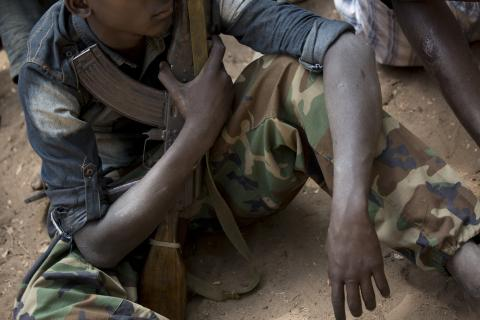 South Sudan. A child sits while holding a gun.